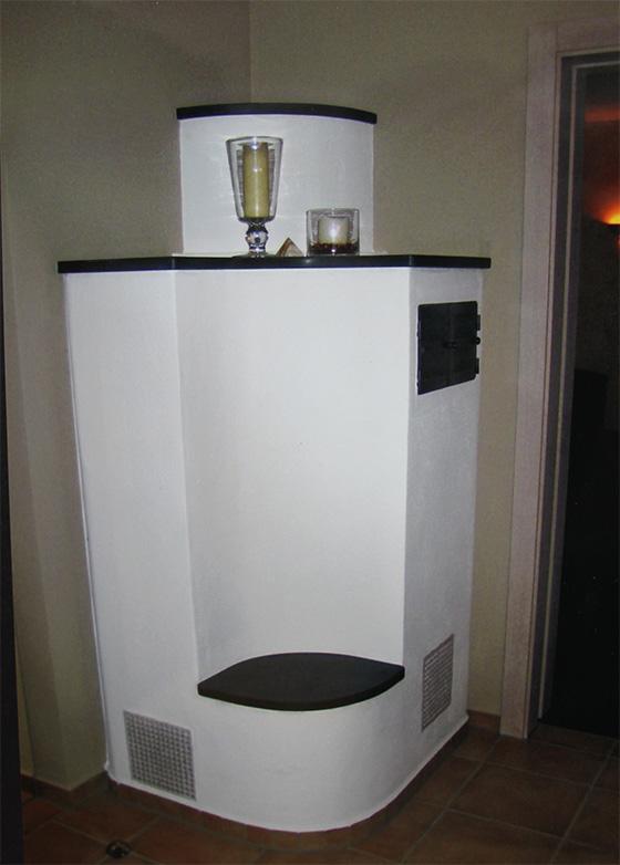 Vom Nebenraum befeuerter Ofen mit Sitzbank