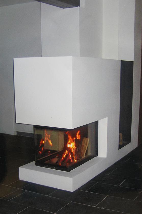 Panoramakamin mit dreiseitiger Scheibe und seitlich integrierter Holzlege